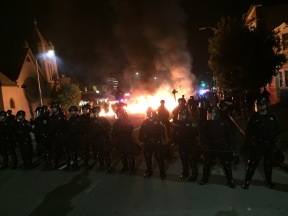 Police advance past a fire set by protesters in Oakland, California, Nov. 25, 2014. (Alex Emslie/KQED)