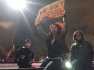 A woman holding a sign in reference to Eric Garner is about to be shoved off a dividing wall on Interstate 880 in Oakland on Dec. 5. (Alex Emslie/KQED)