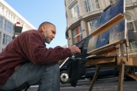 """Vaeriy Novy creates and sells oil paintings on the corner of O'Farrell and Stockton streets on Feb. 27, 2011. Novy, who came to the U.S. from Moscow two years ago, said he designs the urban and natural landscapes in his head. """"To start, I make this,"""" he said pointing to a dark shape near the center of one of his paintings. """"It might be a car. It might be a figure."""" (Alex Emslie)"""
