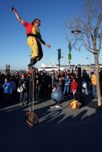 Alex Griffiths rides a tall unicycle in a street performance at Fisherman's Wharf in Sn Francisco on Feb. 27, 2011. Griffiths, part of the four-member Sardine Family Circus, came to San Francisco from England to study acrobatics. (Alex Emslie)