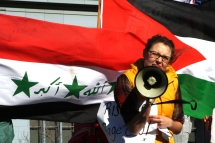 """Code Pink intern Chelsea Byers yells her support of the Iraqi people on their """"Day of Rage"""" from San Francisco's Embarkadero on Feb. 25. (Alex Emslie)"""