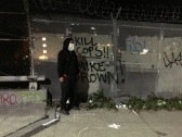 A man in a mask stands near a spray painted message on Dec. 5, 2014 in Oakland, California. (Alex Emslie/KQED)