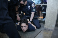 City College student Otto Pippenger is detained by SFPD and City College police officers outside an administration building. Students and teachers protesting decisions by Special Trustee Robert Agrella were stopped by campus and San Francisco police from entering the college's administration building on Thursday, March 13, 2014. (Alex Emslie/KQED)