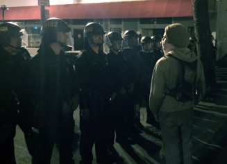 A man in a mask squares off with police in riot gear at Broadway and Seventh Street in Oakland on Dec. 5. (Alex Emslie/KQED)