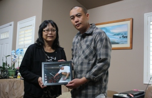 Christine Goias and Matt Chang hold a photo of Errol Chang, who was killed by Daly City SWAT officers in March. (Alex Emslie/KQED)