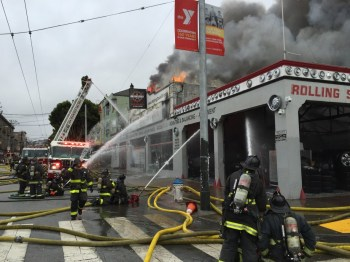 San Francisco firefighters work to contain a November blaze at a tire and wheel shop at 16th and Shotwell streets. An adjacent apartment building was badly damaged, displacing about 20 residents. (Alex Emslie/KQED)