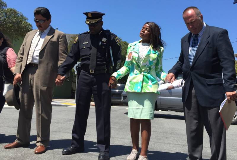 SFPD Homicide Inspector Gianrico Pierucci, Chief Toney Chaplin, Paulette Brown and Inspector Jim Spillane pray on Aug. 12, 2016, at the scene where Aubrey Abrakasa Jr. Was shot dead approximately 10 years ago. (Alex Emslie/KQED)