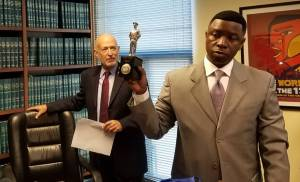 Flanked by his attorney Dan Siegel, Oakland police Sgt. James 'Mike' Gantt holds up an 'officer of the year' award before speaking to reporters about a legal claim he filed against Oakland on Tuesday, Nov. 1, 2016. (Alex Emslie/KQED)