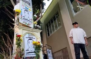 José Góngora Pat flanks a memorial for his brother, Luís Góngora Pat, on Oct. 7. (Alex Emslie/KQED)